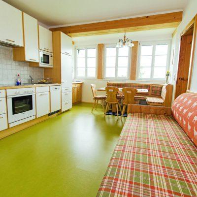 Die großzügige Wohnküche mit neuem Boden und neuer Tapezierung